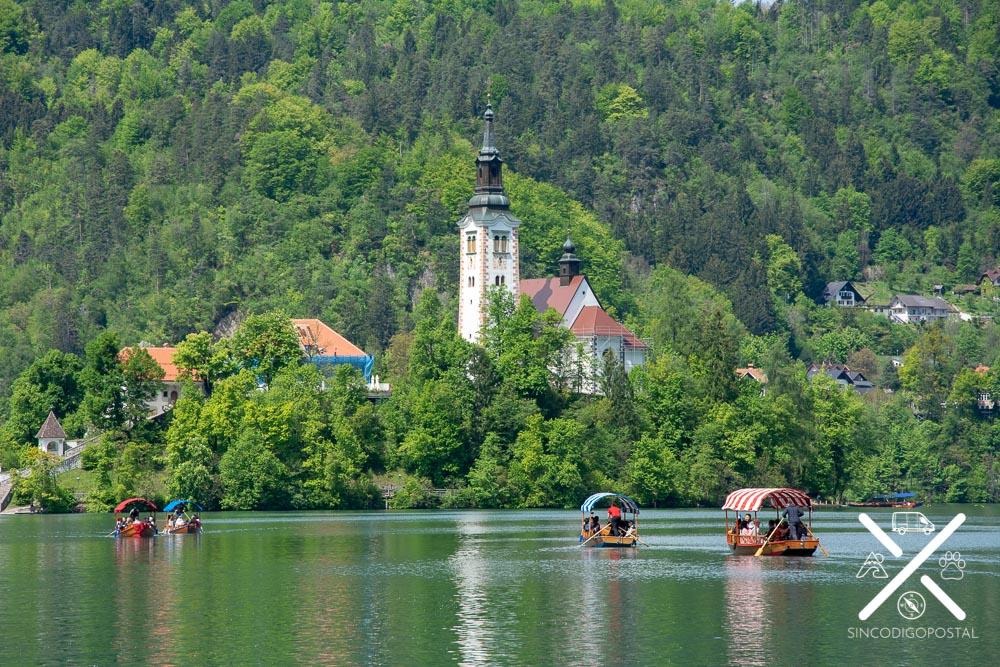 Isla y barcas llegando al centro del Lago Bled