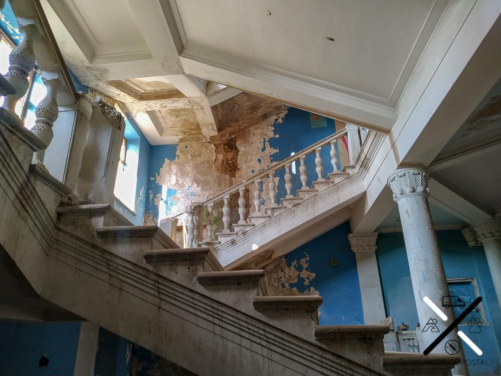 Escaleras que contrastan con las paredes azules en muy mal estado